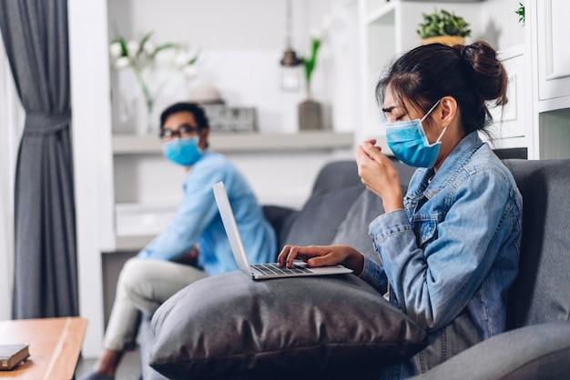 Młoda para azjatyckich za pomocą laptopa pracy i wideokonferencji spotkanie online czat w kwarantannie dla koronawirusa w masce ochronnej z dystansem społecznym w domu. praca z domu koncepcja