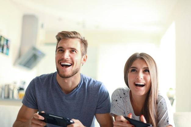 Młoda para bawi się grając w gry wideo w domu