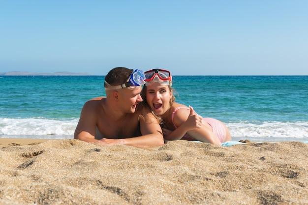 Młoda para bawi się latem na plaży i pokazuje kciuk w górę