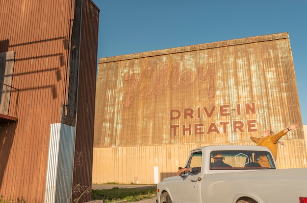 Młoda para bawi się podczas podróży samochodem w kinie samochodowym