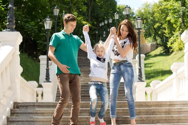 Młoda para bawi się z uroczą małą dziewczynką