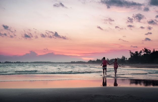 Młoda para biegnie wzdłuż plaży o zachodzie słońca, tropikalny zachód słońca na wyspie