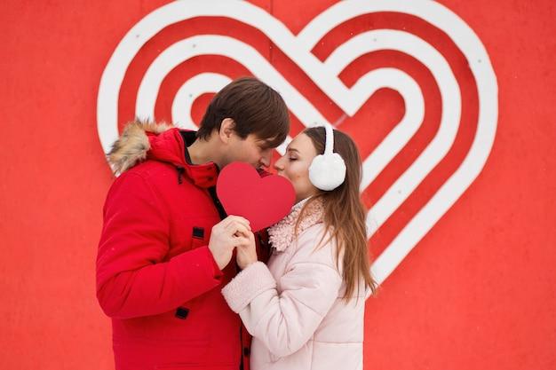 Młoda para całuje i trzyma papierowe serce w pobliżu wielkiego serca na ścianie.