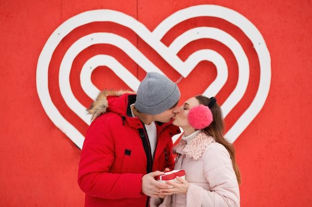 Młoda para całuje i trzyma serce pudełko w pobliżu wielkiego serca na ścianie.