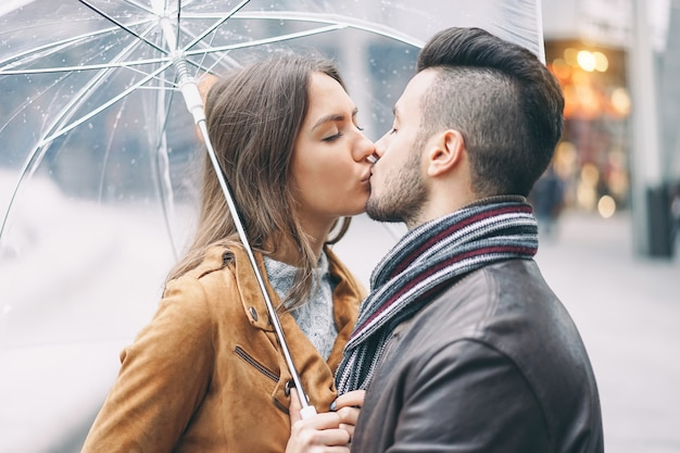 Młoda para całuje pod parasolem w deszczowy dzień w centrum miasta