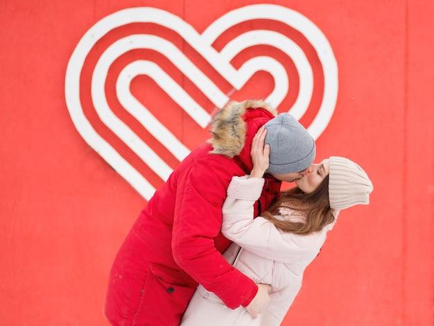 Młoda para całuje się w mieście, w pobliżu wielkiego serca na ścianie. walentynki