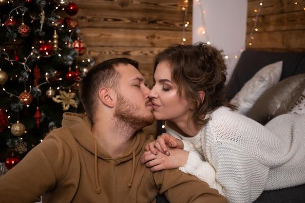 Młoda para całuje w domu w czasie świąt bożego narodzenia w pobliżu pięknie zdobionej choinki