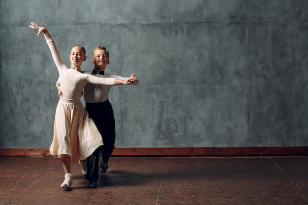 Młoda para chłopiec i dziewczynka tańczy w tańcu towarzyskim walc wiedeński.