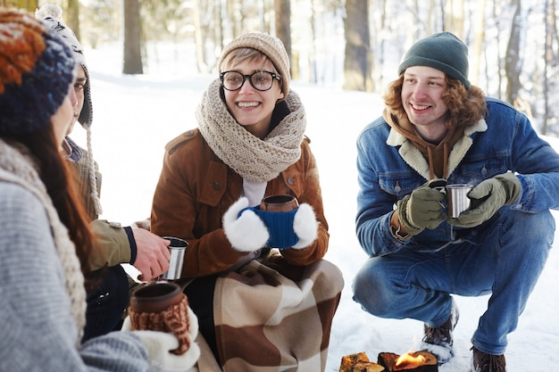Młoda para, ciesząc się napoje w zimowym lesie