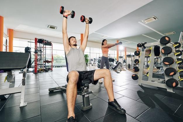 Młoda para, ćwiczenia na siłowni