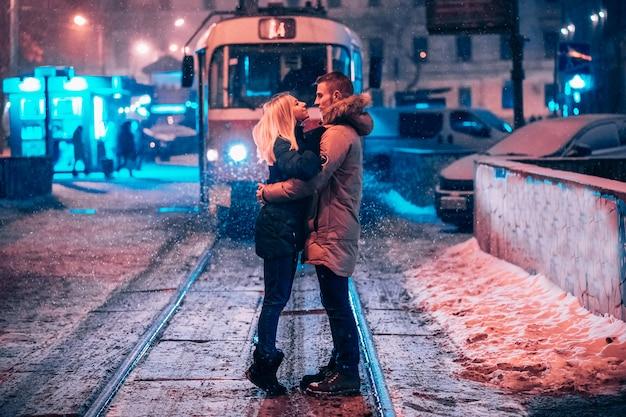 Młoda para dorosłych na zaśnieżonej linii tramwajowej