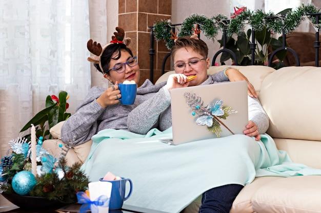 Młoda para dwóch kobiet siedzących na kanapie i pijących gorącą czekoladę w boże narodzenie podczas oglądania filmu na komputerze