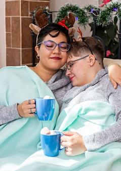Młoda para dwóch kobiet siedzących na kanapie i pijących gorącą czekoladę w boże narodzenie