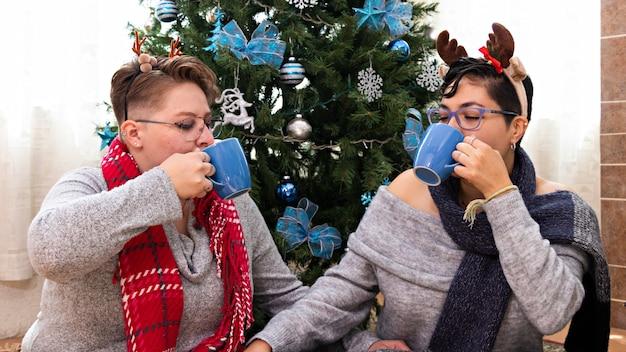 Młoda para dwóch kobiet siedzi przed choinką i pije gorącą czekoladę