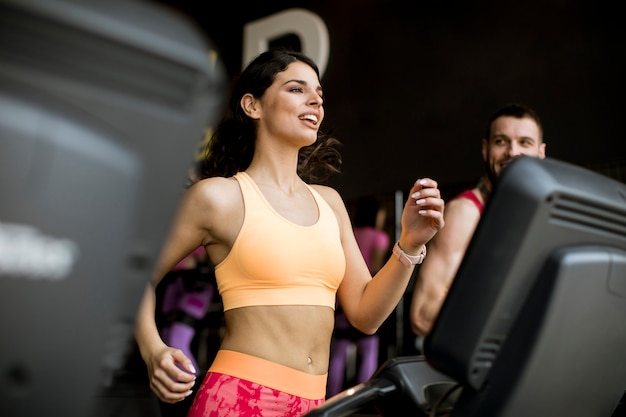 Młoda para działa na bieżni w nowoczesnej siłowni