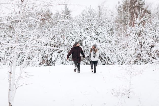 Młoda para działa na polu śnieżnej zimy w pobliżu sosny