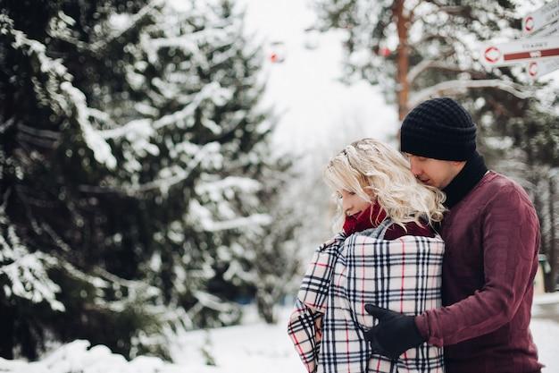 Młoda para dziewczyny i chłopaka, stojąc w śniegu w lesie i pozowanie odwracając się na bok.