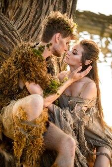 Młoda para elfów w miłości stoi w magicznym lesie na łące plenerowej na naturze