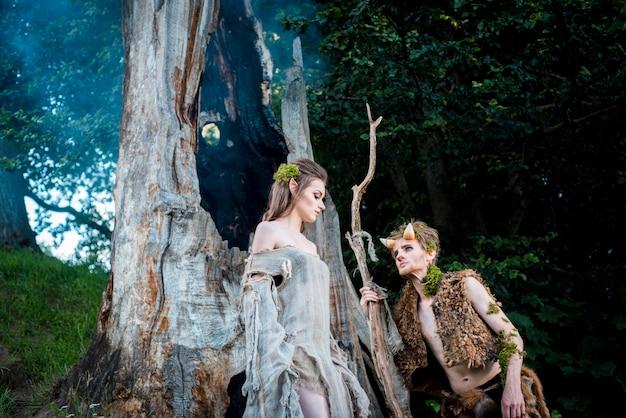 Młoda para elfów w miłości stoi w magicznym lesie plenerowym na naturze.