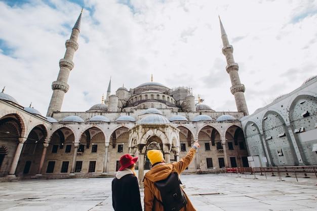 Młoda para europejska chodzi na dziedzińcu błękitnego meczetu w stambule w turcji. podróżnik facet i dziewczyna w żółtych kapeluszach chodzą w zimie stambuł. pochmurny, jesienny dzień w stambule.