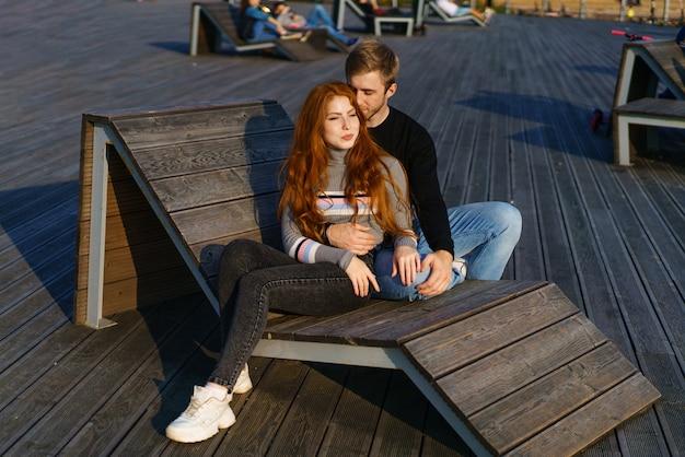 Młoda para facet i dziewczyna z rudymi włosami o kaukaskim wyglądzie w zwykłych ubraniach w słoneczny dzień