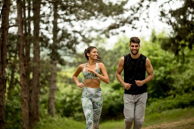 Młoda para fitness działa na leśnym szlaku