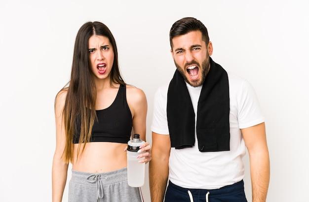 Młoda para fitness kaukaski na białym tle krzyczy bardzo zły i agresywny.