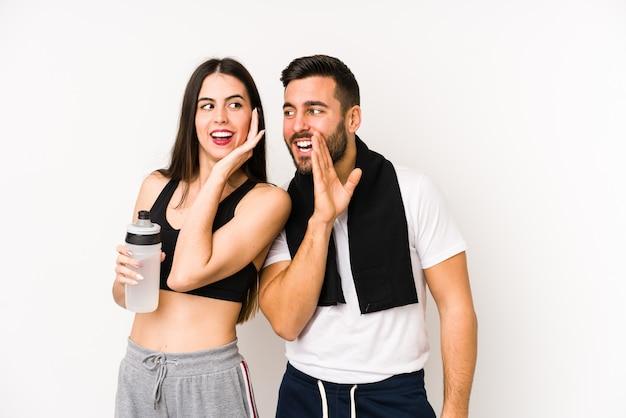 Młoda para fitness kaukaski na białym tle mówi tajną wiadomość o gorącym hamowaniu i patrzy na bok