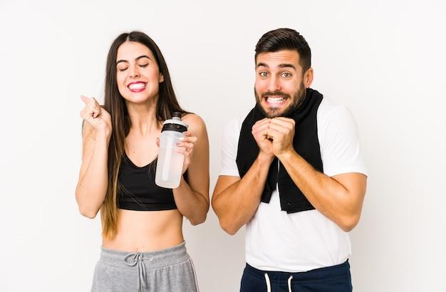 Młoda para fitness kaukaski na białym tle podnosząc pięść, czując się szczęśliwy i odnoszący sukcesy.