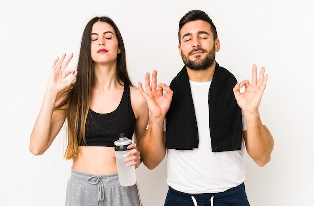 Młoda para fitness kaukaski na białym tle relaksuje się po ciężkim dniu pracy, wykonuje jogę.