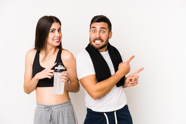 Młoda para fitness kaukaski zszokowany, wskazując palcami wskazującymi na puste miejsce.