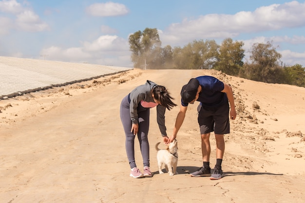 Młoda para fitness pieszczoty swojego małego psa w piasku.