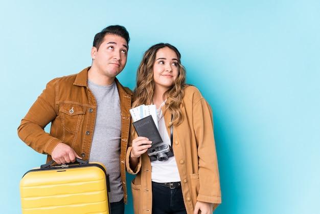 Młoda para gotowa do podróży na białym tle marzy o osiągnięciu celów