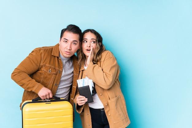 Młoda para gotowa do podróży w odosobnieniu mówi sekretną wiadomość o gorącym hamowaniu i patrzy na bok