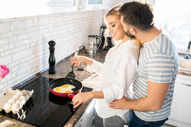 Młoda para gotowania śniadanie w kuchni