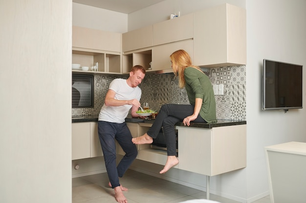 Młoda para gotuje i je obiad w kuchni swojego małego mieszkania