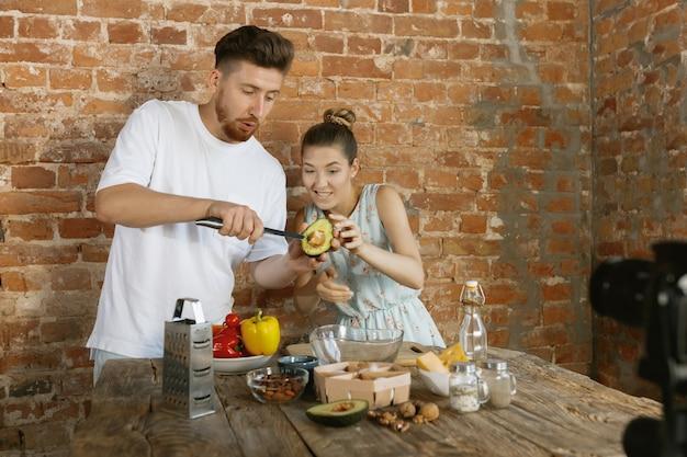 Młoda para gotuje i nagrywa wideo na żywo do vloga i mediów społecznościowych