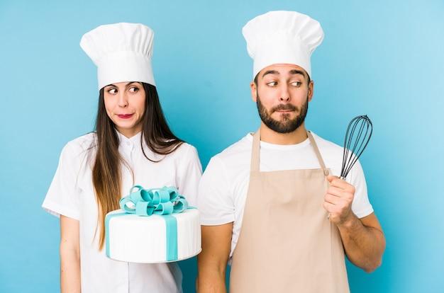 Młoda para gotuje razem ciasto gryząc paznokcie, nerwowa i bardzo niespokojna.