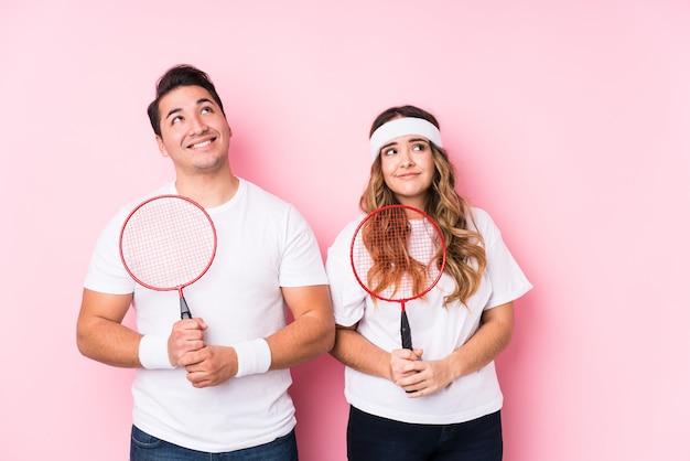 Młoda para gra w badmintona na białym tle marzy o osiągnięciu celów