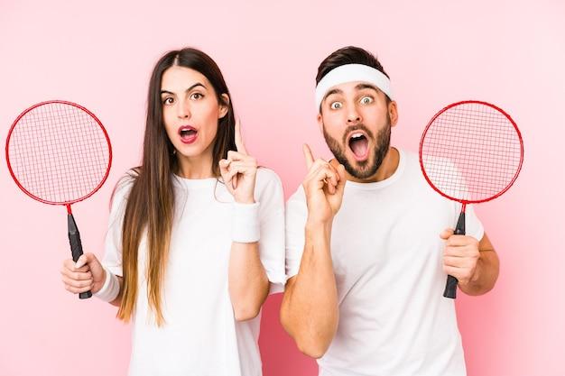 Młoda para gra w badmintona na białym tle pomysł, koncepcja inspiracji.