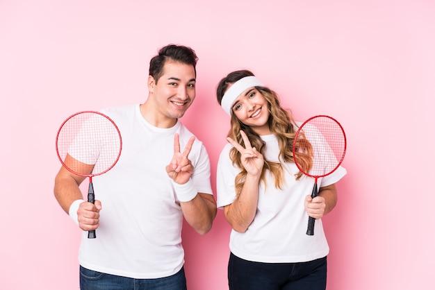 Młoda para gra w badmintona na białym tle radosny i beztroski, pokazując symbol pokoju palcami.