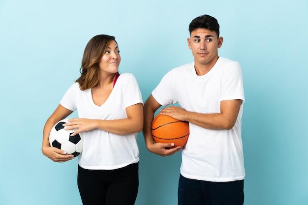 Młoda para gra w piłkę nożną i koszykówkę na niebiesko robi gest wątpliwości podczas podnoszenia ramion