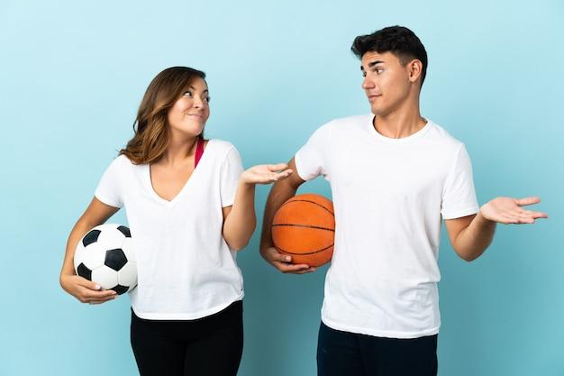 Młoda para gra w piłkę nożną i koszykówkę na niebiesko robi nieistotny gest podczas podnoszenia ramion