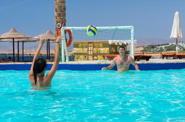 Młoda para gra w piłkę wodną w hotelu w słoneczny letni dzień