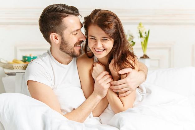 Młoda para heteroseksualna dorosłych, leżąc na łóżku w sypialni