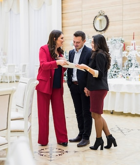Młoda para i kierownik imprezy omawiający plan