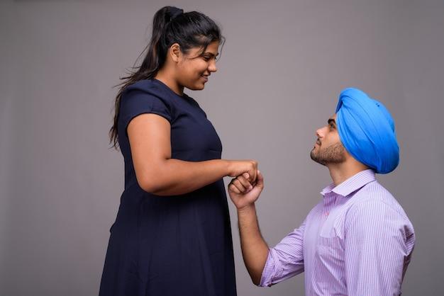 Młoda para indian razem i zakochani na szarej ścianie