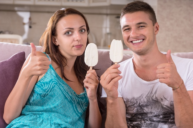 Młoda para je batoniki z lodami i daje kciuk w górę przed kamerą siedząc na kanapie w domu