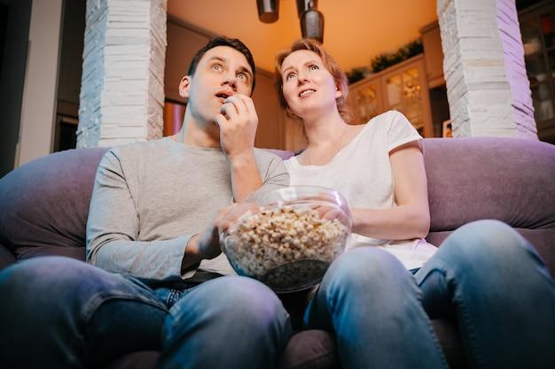 Młoda para jedząca popcorn i oglądająca film w domu na kanapie bardzo się boi