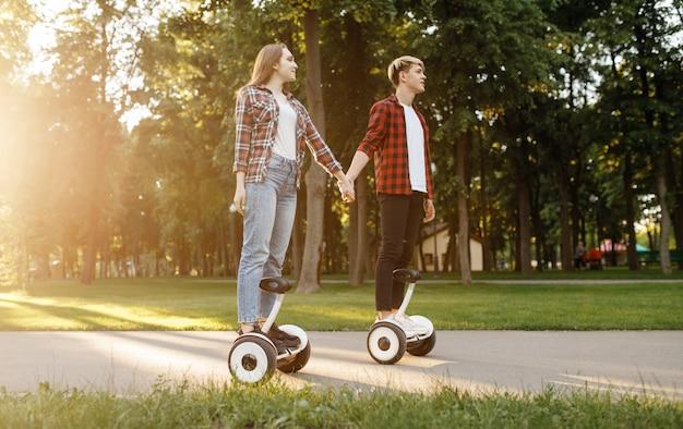 Młoda para jedzie na pokładzie żyroskopu w lato park o zachodzie słońca.